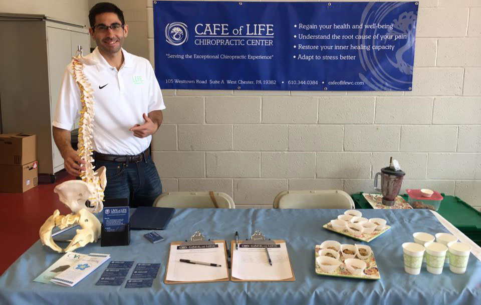 Dr. Raj displaying chiropractic sports injuries discussion table in West Chester, PA